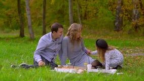Το Mom και ο μπαμπάς κάθονται σε ένα κάλυμμα στο πάρκο, μια κόρη έρχεται και δίνει ένα λουλούδι στη μητέρα της απόθεμα βίντεο