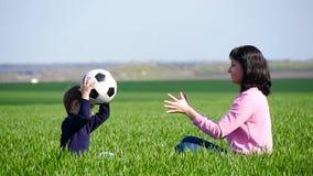 Το Mom και το παιδί κάθονται στην πράσινη χλόη και παίζουν με τη σφαίρα, ρίχνοντας το το ένα στο άλλο φιλμ μικρού μήκους
