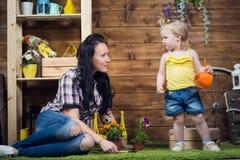 Το Mom και το παιδί φυτεύουν τα λουλούδια στοκ εικόνα