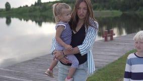Το Mom και τα παιδιά περπατούν στο πάρκο από τον ποταμό φιλμ μικρού μήκους