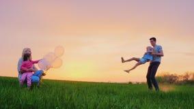 Το Mom και τα παιδιά παίζουν έξω Ο μεγάλος αδερφός περιβάλλει τη νεώτερη αδελφή του, η οικογένεια που έχει τη διασκέδαση απόθεμα βίντεο