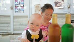 Το Mom και το μωρό σε ένα όμορφο φόρεμα με την πεταλούδα τρώνε σε έναν καφέ στην οδό Τράπεζες με την πράσινη και κίτρινη λεμονάδα φιλμ μικρού μήκους