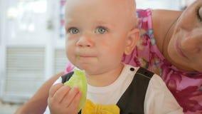 Το Mom και το μωρό σε ένα όμορφο φόρεμα με την πεταλούδα τρώνε σε έναν καφέ στην οδό Παιδί που τρώει ένα κομμάτι της σαλάτας αγγο απόθεμα βίντεο