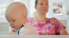 Το Mom και το μωρό σε ένα όμορφο φόρεμα με την πεταλούδα τρώνε σε έναν καφέ στην οδό Παιδί που τρώει ένα κομμάτι της σαλάτας αγγο φιλμ μικρού μήκους