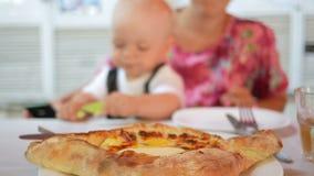Το Mom και το μωρό σε ένα όμορφο φόρεμα με την πεταλούδα τρώνε σε έναν καφέ στην οδό Ψημένο μπισκότο τυριών με το αυγό και το βού φιλμ μικρού μήκους