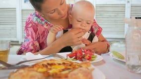 Το Mom και το μωρό σε ένα όμορφο φόρεμα με την πεταλούδα τρώνε σε έναν καφέ στην οδό Το παιδί δοκιμάζει τη σαλάτα πιάτο της μητέρ απόθεμα βίντεο