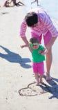 Το Mom και το μωρό στην παραλία έχουν τη διασκέδαση Στοκ Εικόνα