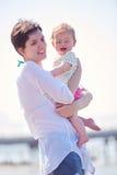 Το Mom και το μωρό στην παραλία έχουν τη διασκέδαση Στοκ Φωτογραφία