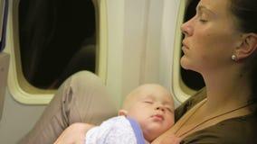 Το Mom και το μωρό στηρίζονται στο αεροπλάνο κατά τη διάρκεια της πτήσης Πτήση νύχτας πέρα από τον ωκεανό Τα μάτια του παιδιού εί απόθεμα βίντεο