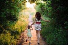 Το Mom κρατά το χέρι της κόρης και περπατά τον περίπατο στη φύση στο φως ηλιοβασιλέματος στοκ εικόνα με δικαίωμα ελεύθερης χρήσης