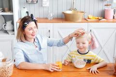 Το Mom κτυπά ελαφρά το αγόρι στο κεφάλι Γιος και νέα μητέρα στην κουζίνα που τρώει το πρόγευμα Στοκ φωτογραφία με δικαίωμα ελεύθερης χρήσης