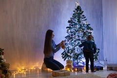Το Mom με το γιο εξωραΐζει το νέο έτος Χριστουγέννων φω'των χριστουγεννιάτικων δέντρων στοκ φωτογραφία με δικαίωμα ελεύθερης χρήσης