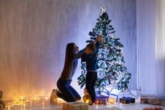 Το Mom με το γιο εξωραΐζει το νέο έτος Χριστουγέννων φω'των χριστουγεννιάτικων δέντρων στοκ εικόνες