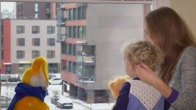 Το Mom με τη συνεδρίαση κοριτσιών παιδιών μικρών παιδιών κοντά στο παράθυρο και απολαμβάνει snowflakes την πτώση χιονιού απόθεμα βίντεο