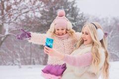 Το Mom ξανθό και λίγη κόρη που ντύνεται στα ρόδινα ενδύματα έχουν τη διασκέδαση και selfie σε ένα κινητό τηλέφωνο στοκ φωτογραφίες με δικαίωμα ελεύθερης χρήσης