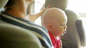 Το Mom πηγαίνει με το παιδί στη πίσω θέση του αυτοκινήτου Το χαριτωμένο ενός έτους βρέφος μικρών παιδιών πηγαίνει στην περιτύλιξη φιλμ μικρού μήκους