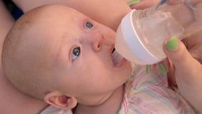 Το Mom που δίνει το μωρό πίνει το νερό από το μπουκάλι απόθεμα βίντεο