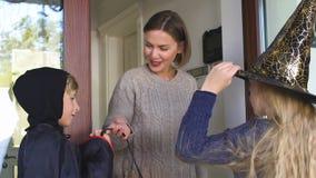 Το Mom που ντύνει τα παιδιά της για το τέχνασμα ή μεταχειρίζεται το παιχνίδι, παράδοση διακοπών αποκριών απόθεμα βίντεο