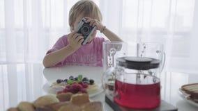 Το Mom προετοιμάζει το πρόγευμα και αυτή τη στιγμή το αγόρι παίζει το φωτογράφο απόθεμα βίντεο