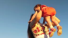 Το Mom ρίχνει την κόρη της μέχρι τον ουρανό παιχνίδια μητέρων με ένα μικρό παιδί ενάντια σε έναν μπλε ουρανό ευτυχές οικογενειακό φιλμ μικρού μήκους