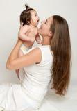 Το Mom ρίχνει το μωρό και το φιλί μωρών, το παιχνίδι και την κατοχή της διασκέδασης Στοκ φωτογραφίες με δικαίωμα ελεύθερης χρήσης