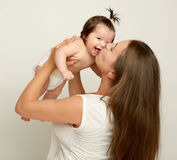 Το Mom ρίχνει το μωρό και το φιλί μωρών, το παιχνίδι και την κατοχή της διασκέδασης Στοκ εικόνες με δικαίωμα ελεύθερης χρήσης