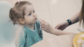 Νέα όμορφη μητέρα με την λίγη συνεδρίαση κορών σε έναν καφέ Το Mom σκουπίζει το στόμα της με μια πετσέτα απόθεμα βίντεο