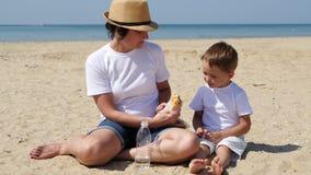 Το Mom ταΐζει το παιδί της με τα burgers στην αμμώδη ακτή απόθεμα βίντεο