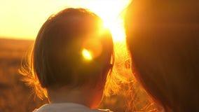 Το Mom την κρατά λίγη κόρη στα όπλα της ευτυχές ηλιοβασίλεμα οικογενειακής προσοχής στο θερμό θερινό βράδυ στο πάρκο απόθεμα βίντεο