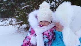 Το Mom την κρατά λίγη κόρη στα όπλα της και περπατά στο άσπρο χιόνι στο πάρκο το χειμώνα και χαμογελά Παιδί και μητέρα επάνω απόθεμα βίντεο