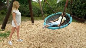 Το Mom τινάζει την κόρη της σε μια ταλάντευση μια αιώρα στο λούνα παρκ στην πόλη 4k, διάστημα αντιγράφων φιλμ μικρού μήκους