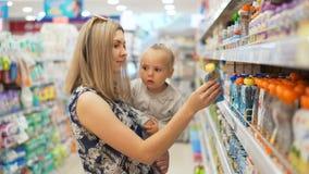 Το Mum μαζί με την κόρη ψάχνει τον πουρέ και τους χυμούς φρούτων παιδιών ` s απόθεμα βίντεο