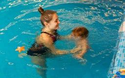 Το Mum μαθαίνει το παιδί για να επιπλέει στη λίμνη Στοκ Φωτογραφίες