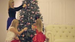 Το Mum με τις κόρες διακοσμεί το χριστουγεννιάτικο δέντρο στη νέα παραμονή έτους απόθεμα βίντεο