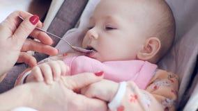 Το Mum ταΐζει με ένα κουτάλι το χαριτωμένο νεογέννητο πουρέ μωρών της κινηματογράφησης σε πρώτο πλάνο κολοκυθιών φιλμ μικρού μήκους