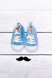 Το Mustache και τα μπλε παπούτσια παιδιών ` s στέκονται σε ένα άσπρο ξύλινο backg Στοκ Εικόνα