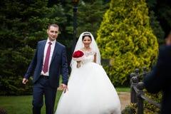 Το Newlywed valentynes που θέτει σε ένα ρομαντικό ευρωπαϊκό πάρκο με αυξήθηκε Στοκ Εικόνα