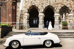 Το Newlyweds περπατά επάνω τα σκαλοπάτια της εκκλησίας και του παλαιού άσπρου αυτοκινήτου Στοκ Εικόνα