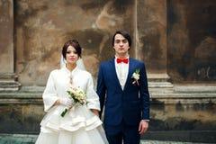 Το Newlyweds φαίνεται σοβαρά στεμένος πίσω από έναν παλαιό καθεδρικό ναό Στοκ Φωτογραφίες