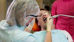 Το Orthodont θεραπεύει τα δόντια ενός ασθενή που έχει έρθει να φροντίσει για τη στοματική κοιλότητα απόθεμα βίντεο