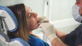Το Orthodontist εξετάζει με τη βοήθεια του καθρέφτη τη στοματική κοιλότητα ενός νέου ασθενή απόθεμα βίντεο