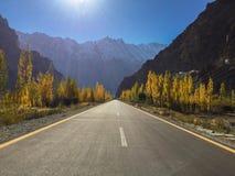 Το Passu το φθινόπωρο παρουσιάζει το σαφή μπλε ουρανό, τα κίτρινα δέντρα λευκών και καλυμμένα χιόνι βουνά στοκ φωτογραφία με δικαίωμα ελεύθερης χρήσης