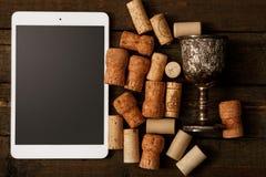 Το PC ταμπλετών και το κρασί βουλώνουν Στοκ Εικόνες