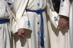 Το Penitents με τις άσπρες τινίκ συλλέγει του χεριού κατά τη διάρκεια μιας πομπής της ιερής εβδομάδας Στοκ Εικόνες