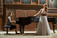 Το pianist γυναικών παίζει το πιάνο και τον όμορφο τραγουδιστή Στοκ Εικόνες