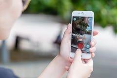 Το Pokemon πηγαίνει app με Krabby pokemon πιάνοντας στο iPhone της Apple 6S Στοκ Εικόνες
