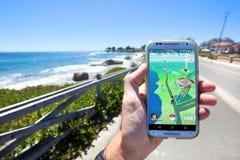 Το Pokemon ΠΗΓΑΙΝΕΙ App που παρουσιάζει στοιχεία χαρτών παιχνιδιών στοκ εικόνες