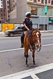 Το Policeofficer οδηγά το άλογό του Στοκ Φωτογραφίες