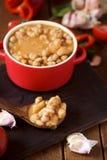 Το Potaje de garbanzos, ισπανικά chickpeas μαγειρεύει σε κατσαρόλα, σε έναν ξύλινο πίνακα Στοκ Εικόνες