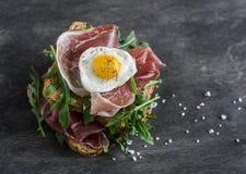 Το Prosciutto, το arugula, και τα τηγανισμένα αυγά ορτυκιών στριμώχνουν στο ξύλινο υπόβαθρο, τοπ άποψη Στοκ εικόνες με δικαίωμα ελεύθερης χρήσης